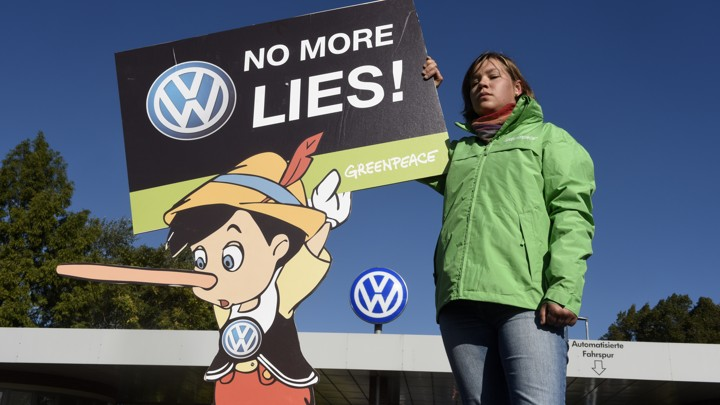 """A Greenpeace activist holds a banner during a protest in front of Volkswagen's """"Sandkamp"""" gate in Wolfsburg"""